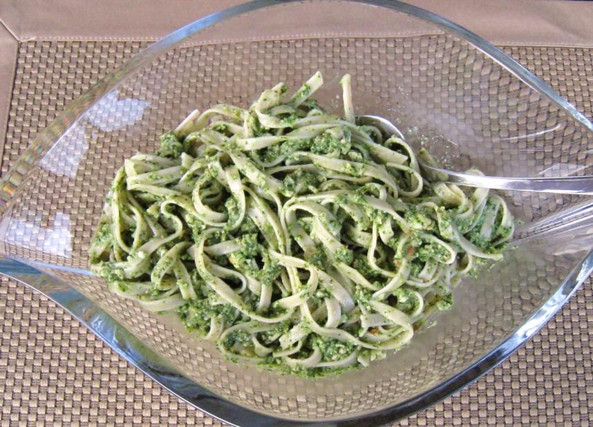 Spinach arugula pesto with fettuccine pasta in glass bowl