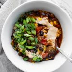 White bowl of 30 minute vegan Mexican chili with green onions