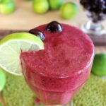 cherry lime slushie in large glass with lime slice