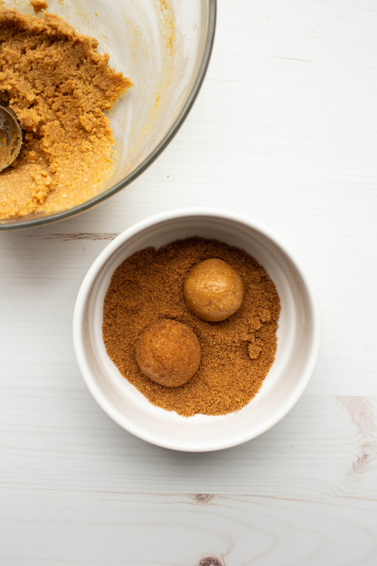 peanut butter cookie balls rolled into bowl of coconut sugar