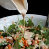 Almond butter dressing pouring over kale salad
