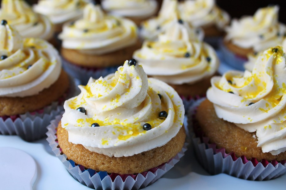 Vegan vanilla cupcakes with white buttercream frosting and yellow sprinkles