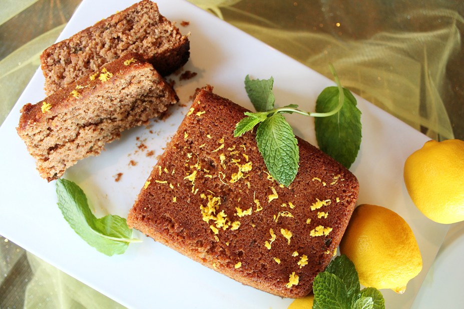 top of loaf with 2 slices and mint leaves around and fresh lemons