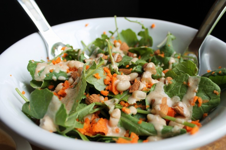 Garlic kale salad with carrots and white beans in white bowl
