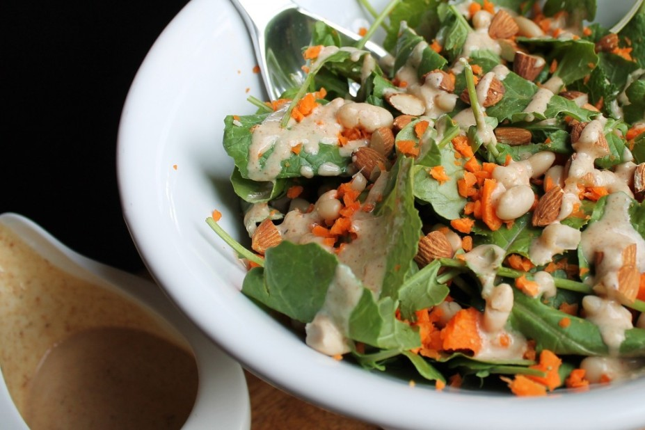 Oil-free almond butter dressing in a bowl next to salad