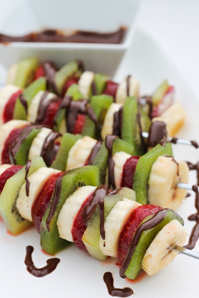 fruit slices on skewers with chocolate drizzled on top
