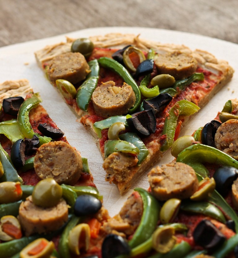 Slice of mashed potato pizza crust with vegan sausage