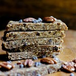 stack of vegan pecan pie bars with chocolate chips on wooden board