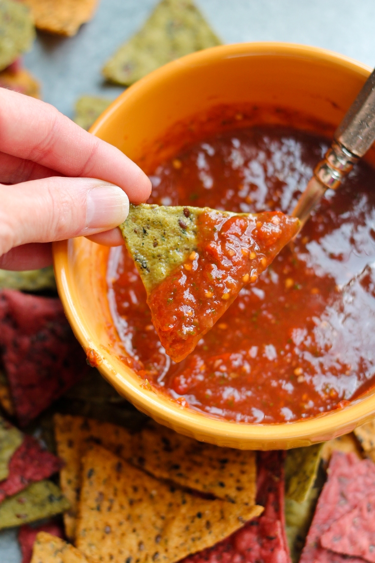 Hand dipping chip into bowl of homemade salsa