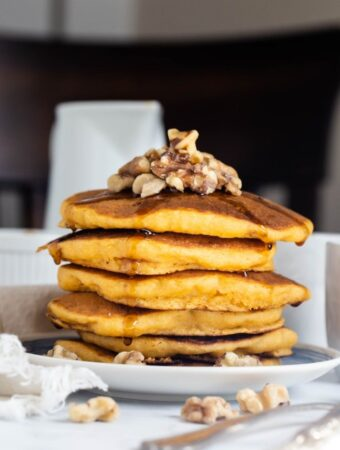stack of sweet potato pancakes with syrup and walnuts on top