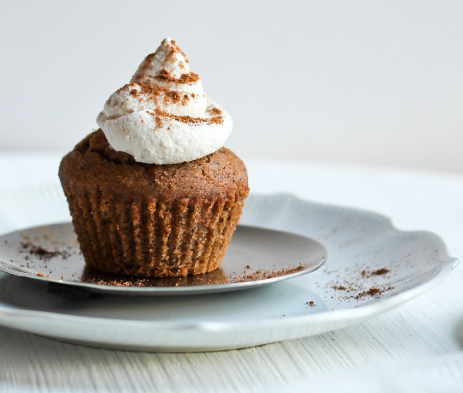 pumpkin muffin on silver plate with whipped cream and pumpkin spice