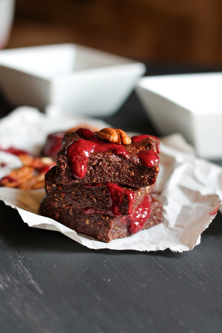 stack of vegan no bake brownies with raspberry coulis on white paper
