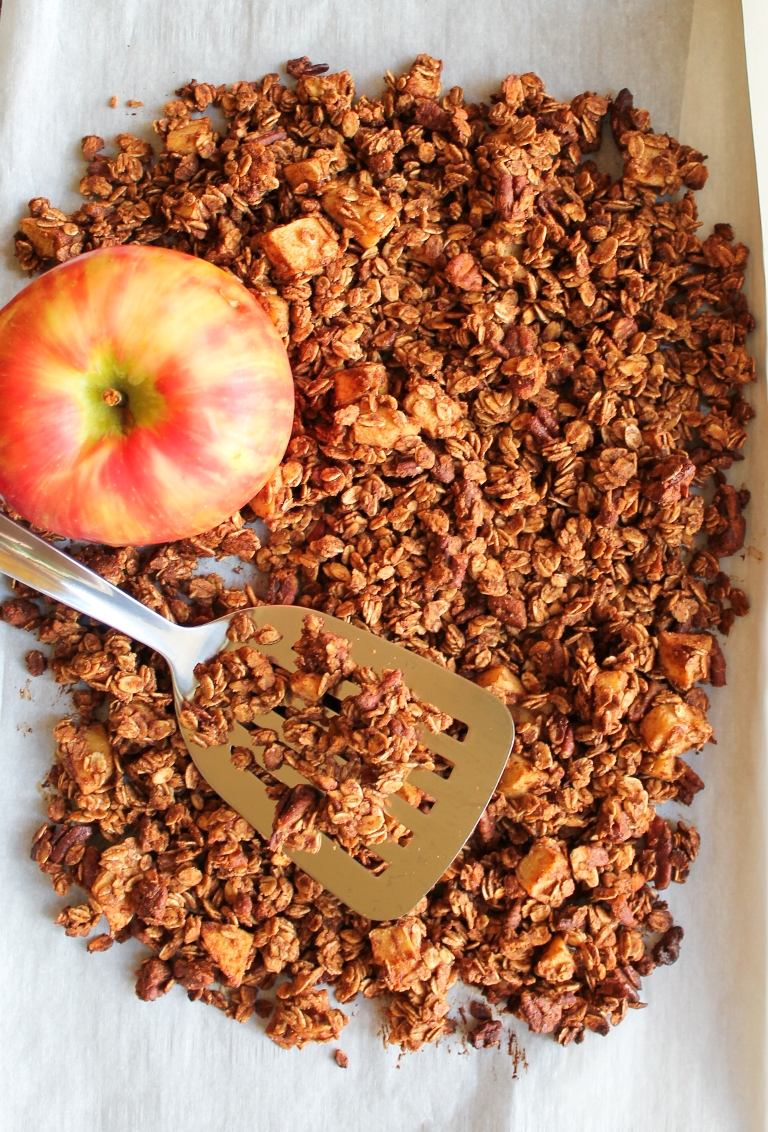 granola spread out on pan with spatula and whole apple