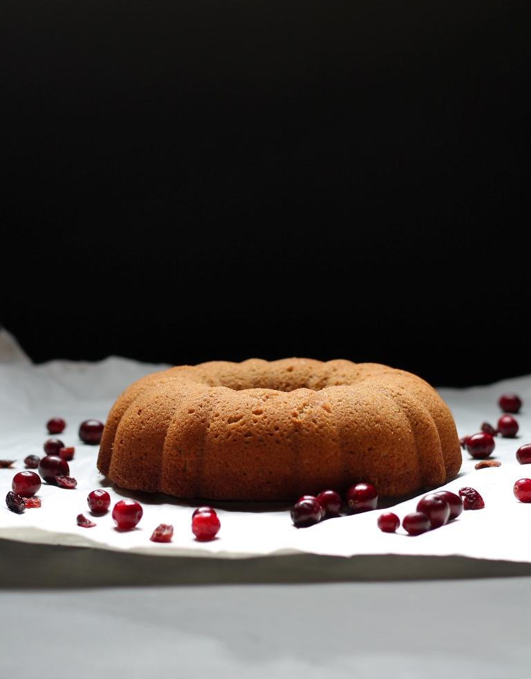 Vegan cranberry bundt cake on white parchment paper