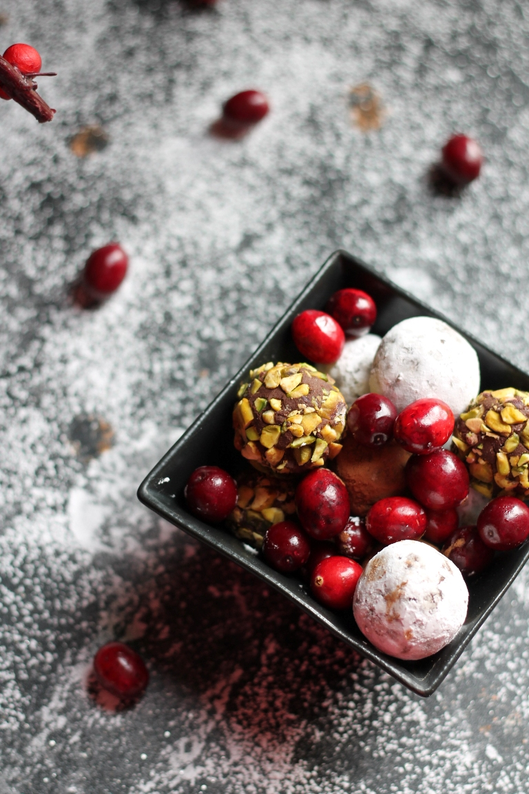 black square bowl of truffles with fresh cranberries