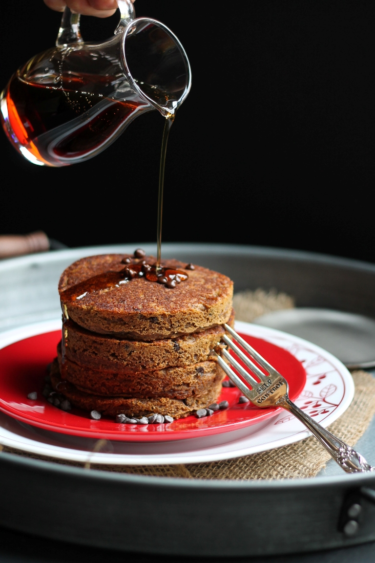 closeup of hand pouring syrup over stack of pancakes with chocolate chips on top