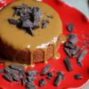 overhead shot of vegan peanut butter glazed cake with dark chocolate pieces on red cake stand