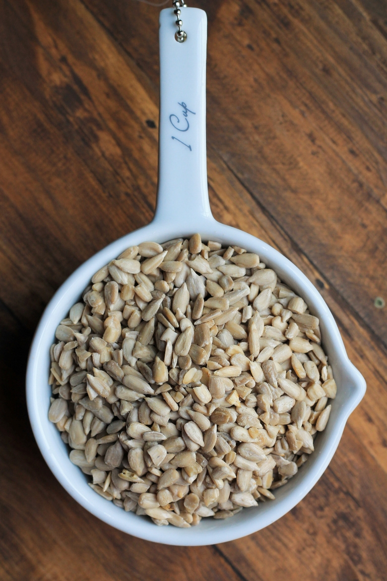 white measuring cup of sunflower seeds