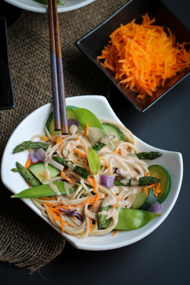 white bowl of buckwheat noodles with almond sauce and snow peas