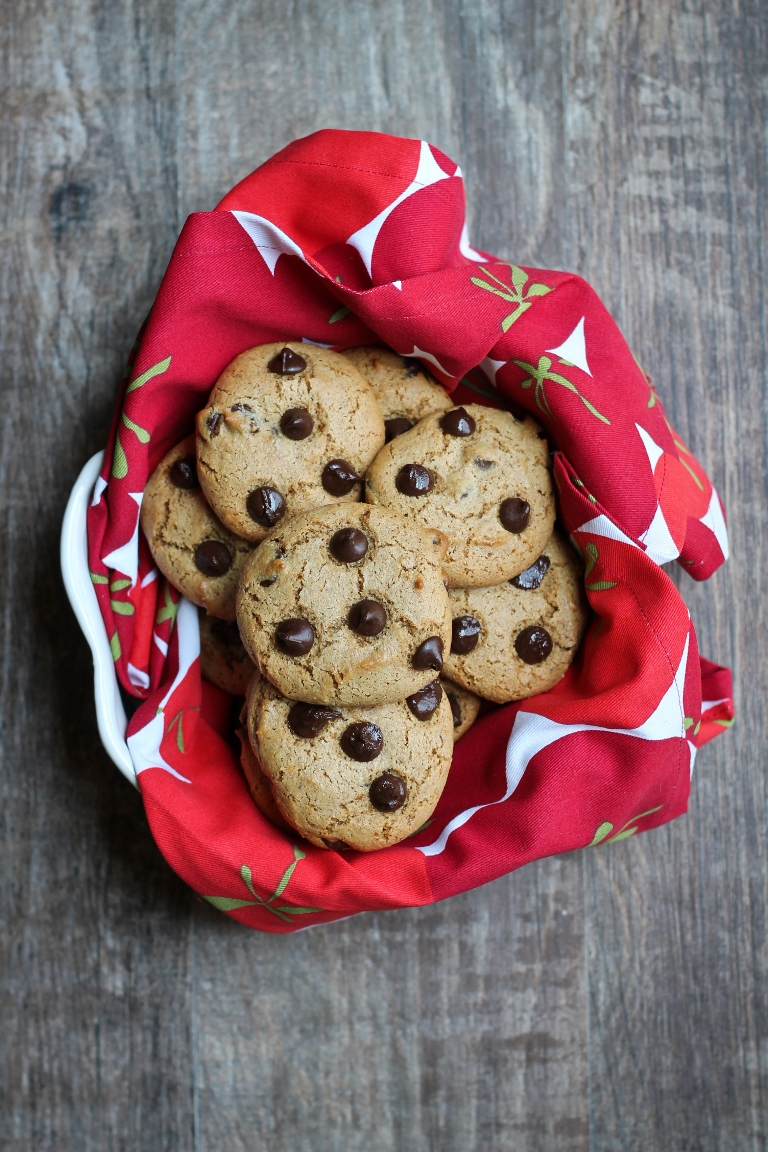A bowl with a red napkin holding several vegan chocolate chip cookies.