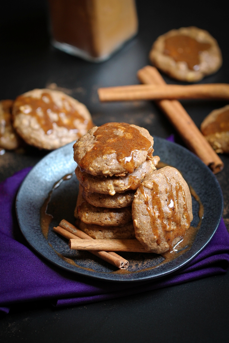 stack of cinnamon oatmeal cookies with caramel dripping down them