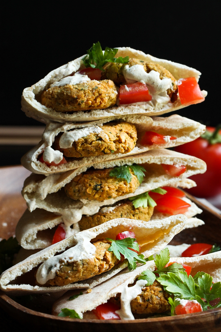 stacked pitas filled with falafel and tomatoes and lemon cream sauce