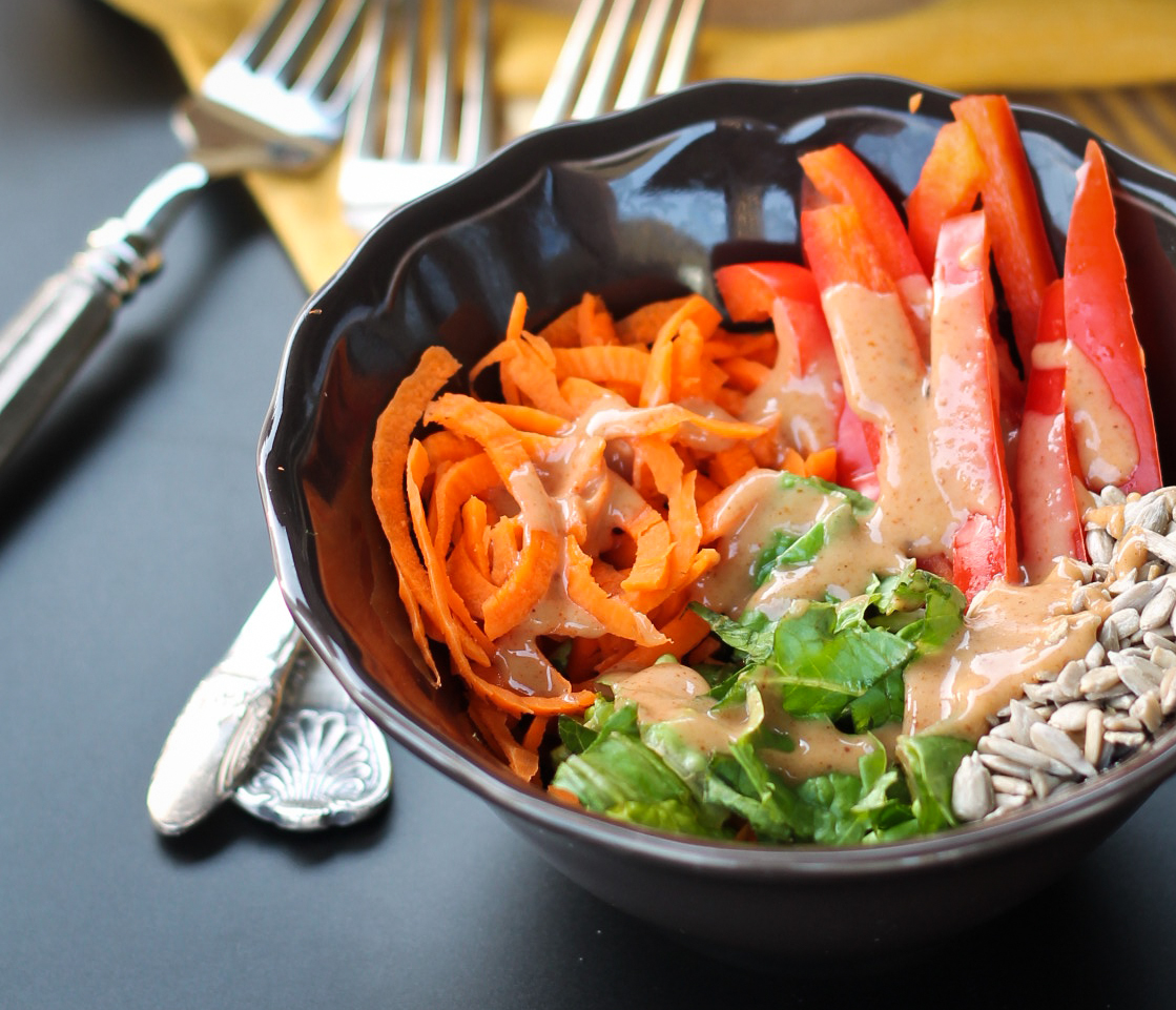 carrot salad in brown bowl with sweet tahini dressing