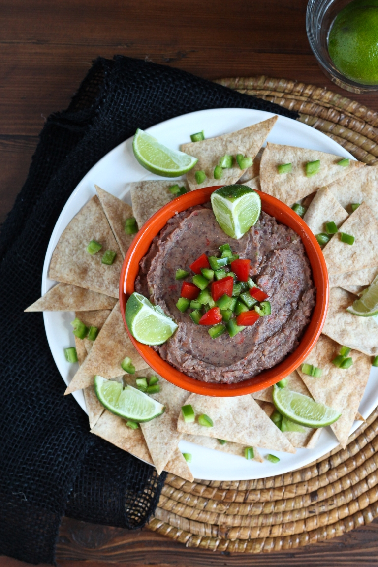Smoky jalapeno black bean dip in bowl on plate with chips