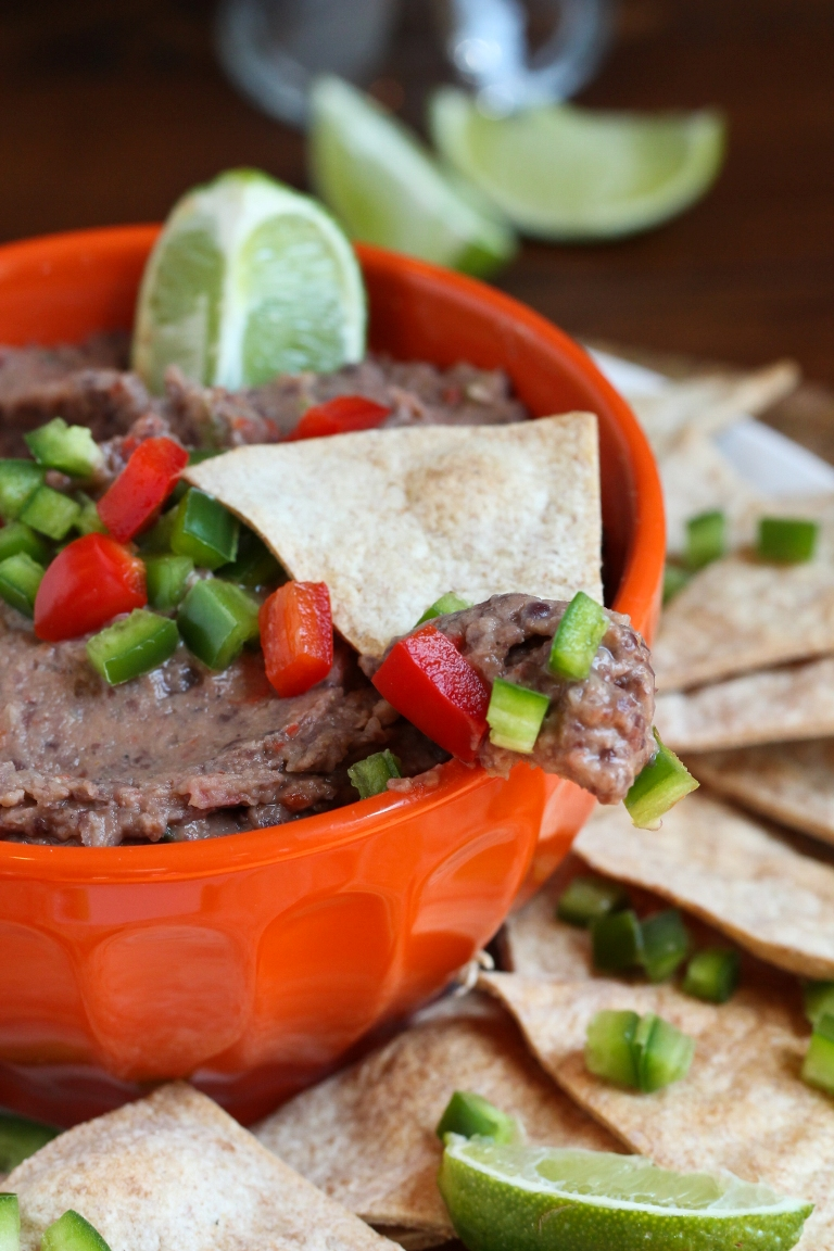 Closeup view of a chip with black bean dip and fresh chopped jalapeno