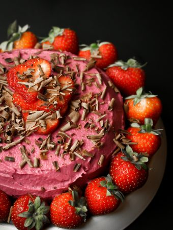 vegan strawberry frosting on chocolate cake with several strawberries on top