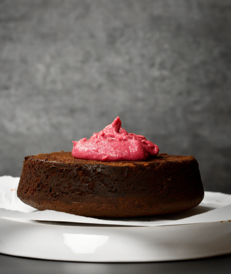 Mound of vegan strawberry frosting on top of chocolate cake