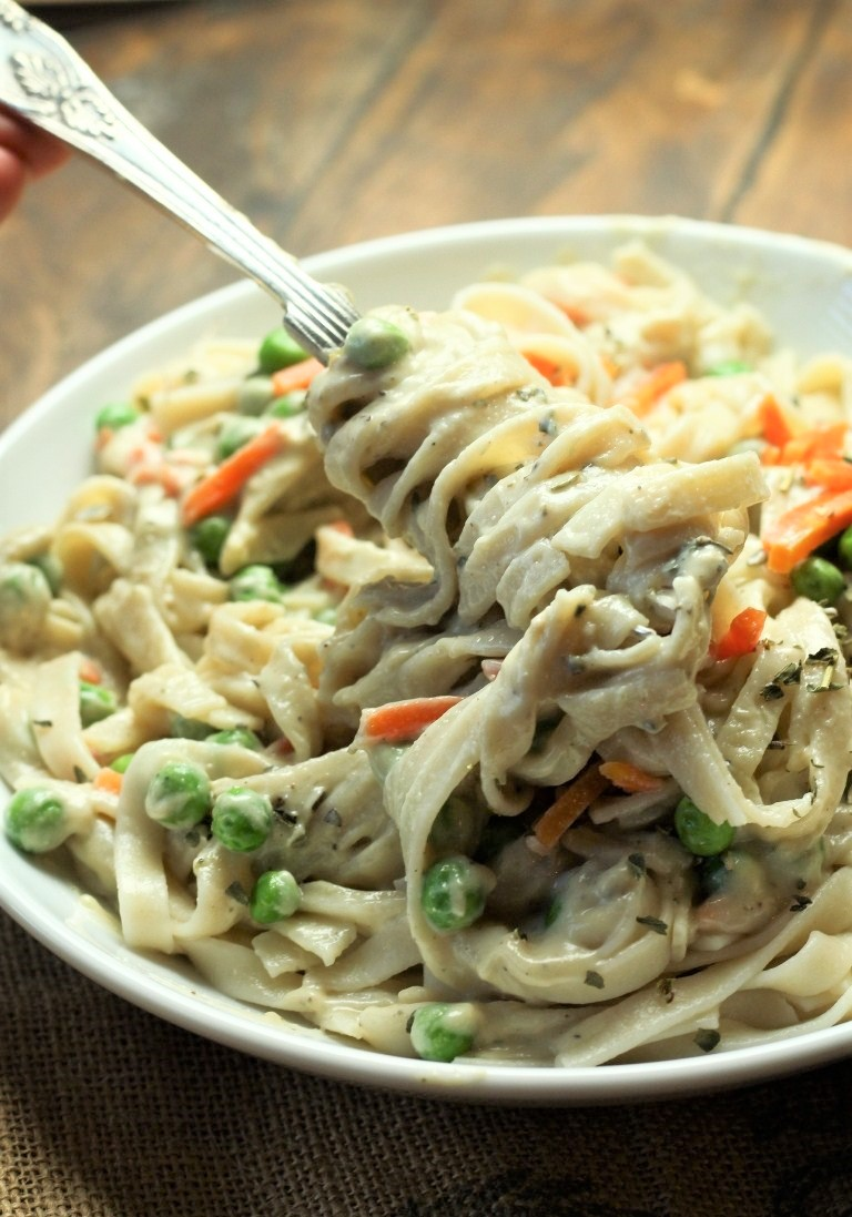 fork twirling alfredo sauce and fettuccini with peas and carrots