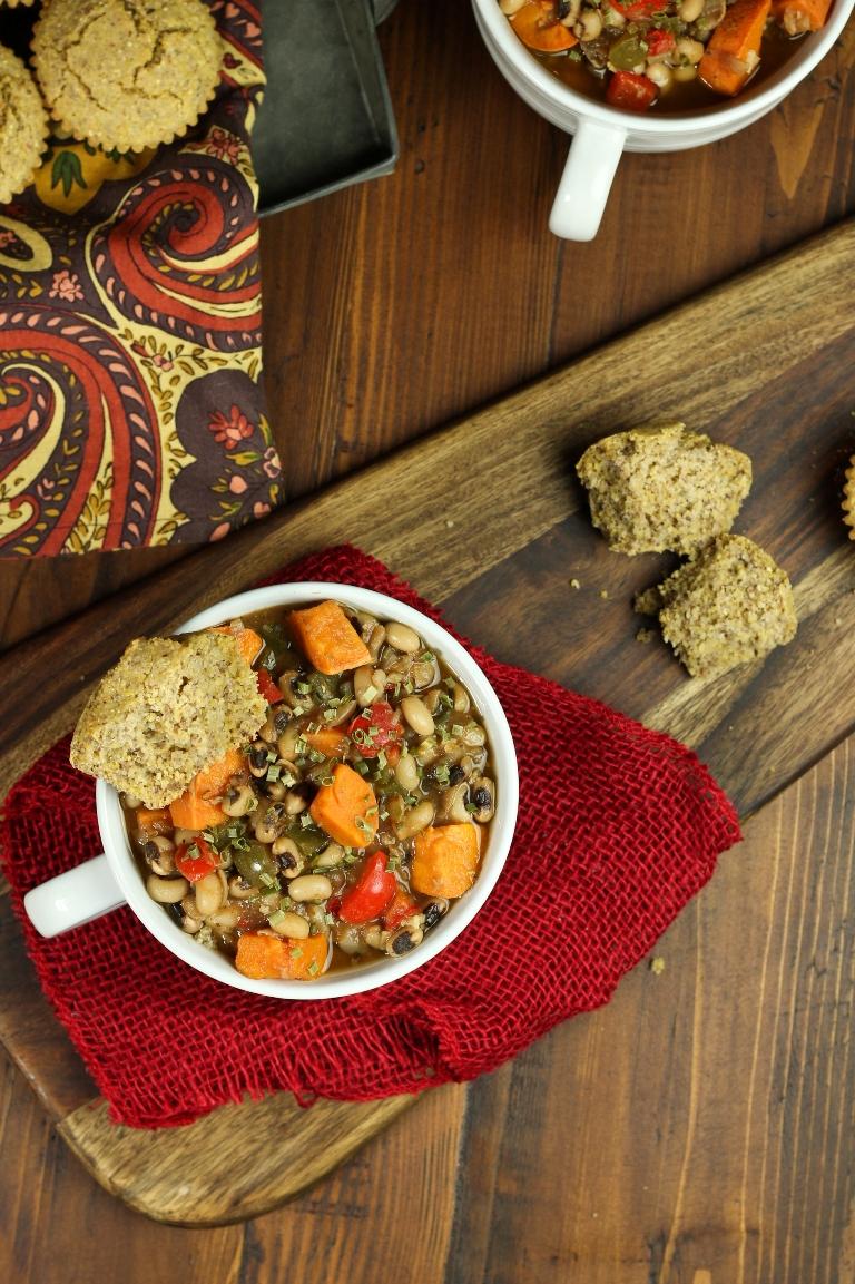 bowl of sweet potato black-eyed pea soup on wood table