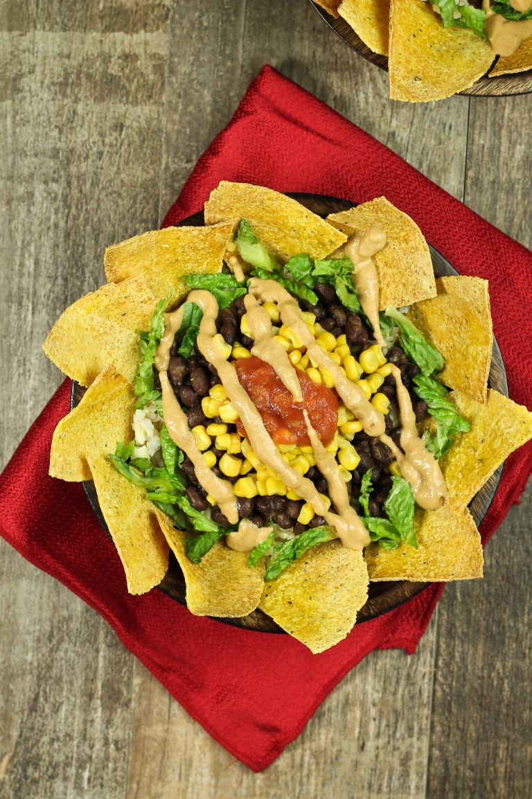 Burrito bowl of chips, corn, black beans and vegan cheese sauce