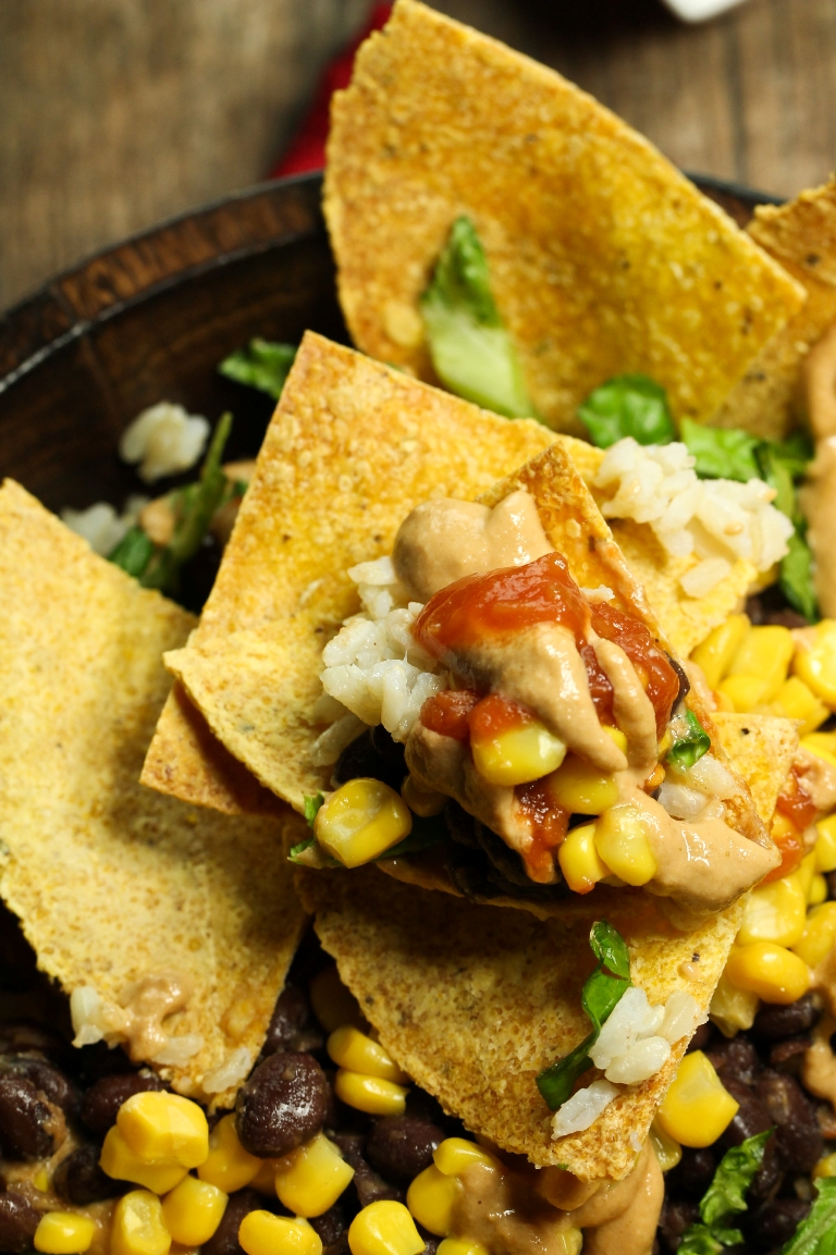 Closeup view of chip with vegan cheese, corn and black beans