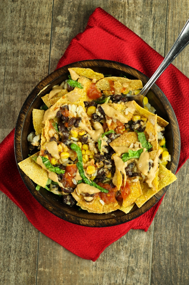 Vegan Mexican burrito bowl with corn, black beans, cheese sauce