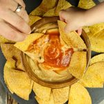 2 hands dipping chips into wood bowl of cheese