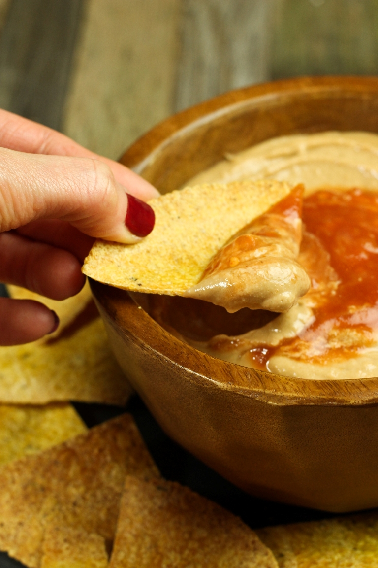 Hand dipping chip into vegan Mexican cheese sauce