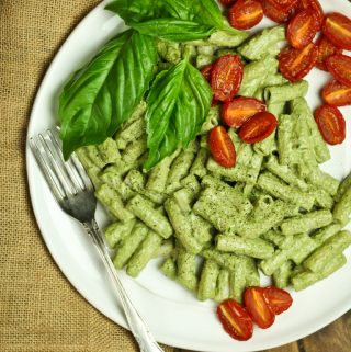 white plate of basil pesto with roasted cherry tomatoes