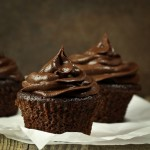 3 chocolate cupcakes with frosting on parchment paper