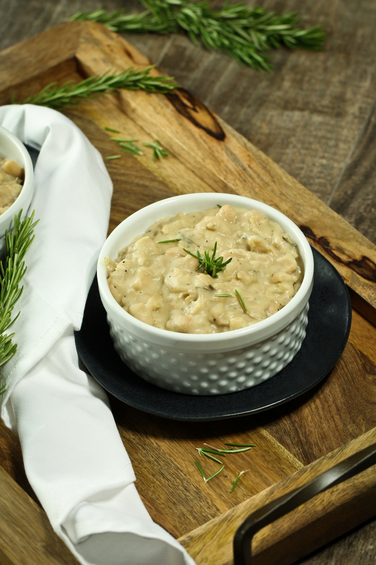 creamy white beans with fresh rosemary in white bowl