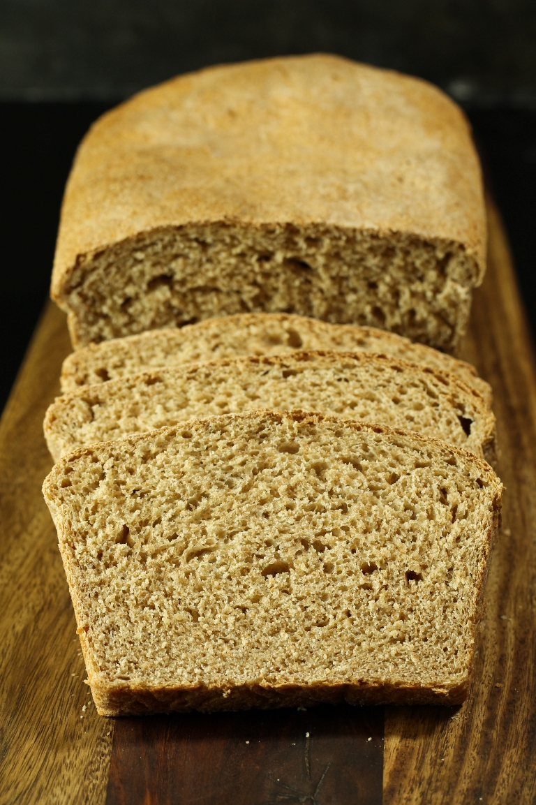 Loaf of vegan spelt bread sliced into slice