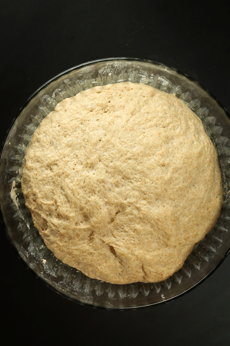 Risen spelt bread dough in glass bowl