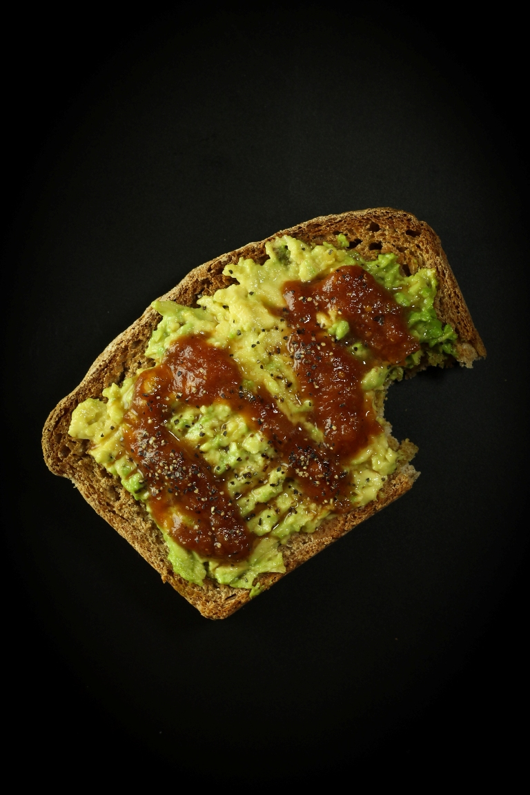 Slice of vegan spelt bread with avocado and bbq sauce on top