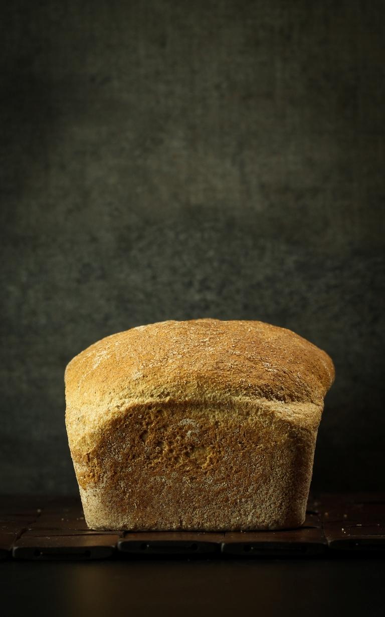 Baked vegan spelt bread on wood platter