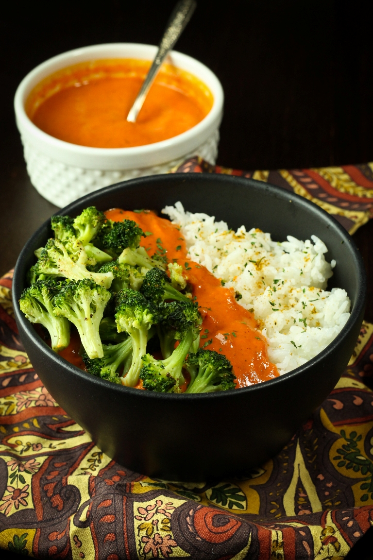 vegan red pepper curry bowl with sauce and broccoli