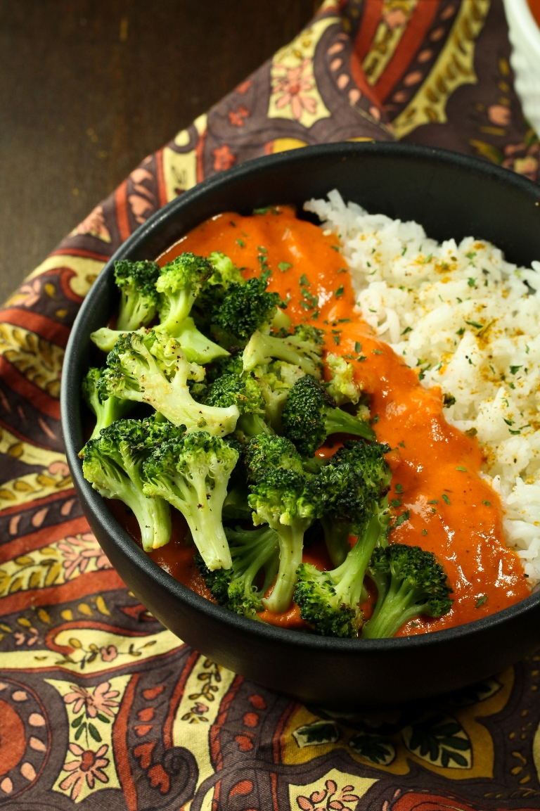 bowl of vegan red pepper curry with rice and broccoli
