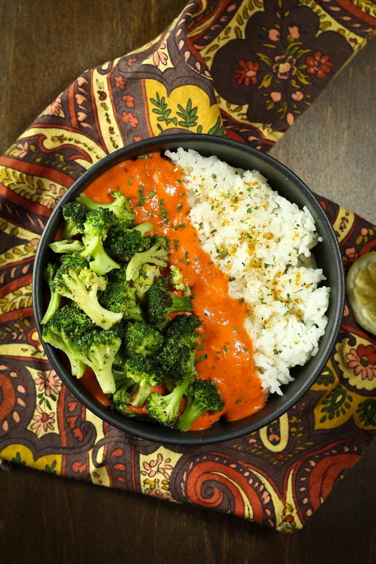 bowl of vegan red pepper curry with rice and broccoli and sauce