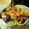 pouring vegan tahini goddess dressing over salad