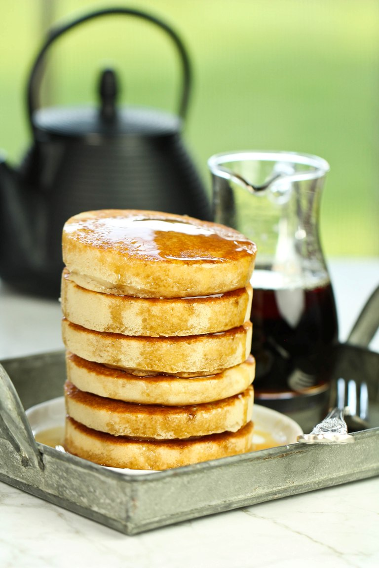 Tall stack of fluffy vegan buttermilk pancakes with syrup on top on a tray.